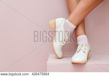 Crossed legs wearing white oxford shoes