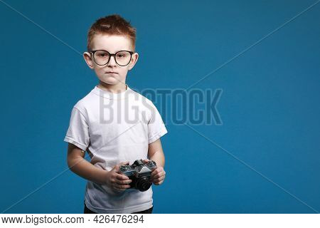 Little Boy Taking A Picture Using A Retro Camera. Child Boy With Vintage Photo Camera Isolated On Bl