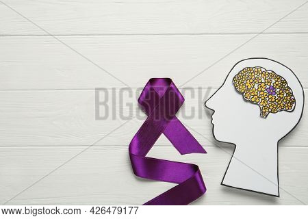 Top View Of Human Head Cutout With Brain And Purple Ribbon On White Wooden Background, Space For Tex
