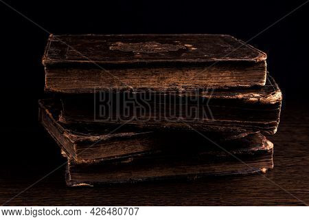 Stack Of Old Worn Shabby Jewish Book In Leather Binding In The Dark. Closeup. Selective Focus. Low K