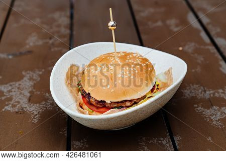 Burger With Patty And Vegetables In A Plate On A Wet Wooden Table.