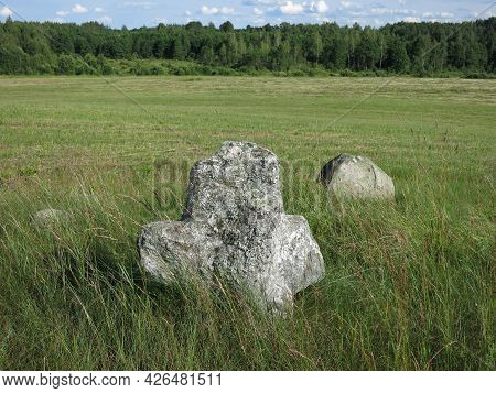 An Old Pagan Cemetery In Belarus. Stone Gray Granite Cross, Humanoid On A Green Meadow In Summer