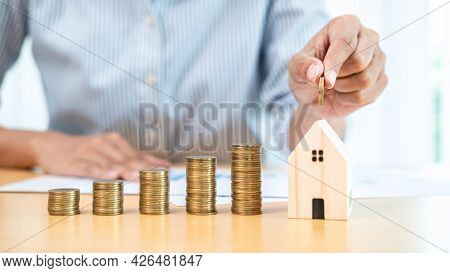 Asian Business Woman Holding Coin To Putting Into House Piggy Bank With Increasing Coins Stack For S