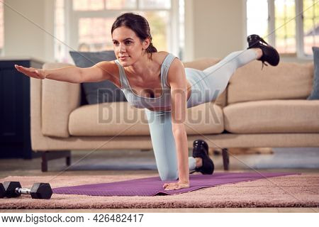 Woman In Fitness Clothing At Home In Lounge Doing Stretches And Exercising With Hand Weights