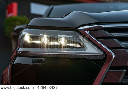 Front Illuminated Headlights Of A Black Luxury Modern Car. Close Up Detail On One Of The Led Headlig