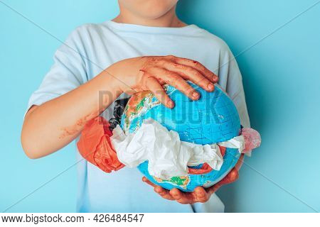 Child Holding Planet Earth With Plastic Disposable Packages From The Middle On A Green Background. S