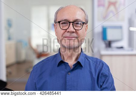 Senior Man Looking At Camera In Dental Office Wainting Consultation. Elderly Male Smiling On Webcam