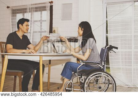 Disabled Beautiful Woman Sitting On A Wheelchair Working With The Male Boyfriend In The Home Office,
