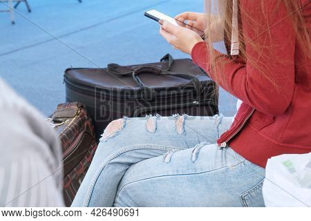 A Girl With Long Hair Holds A Phone In Her Hand While Sitting Next To Her Suitcases At The Train Sta