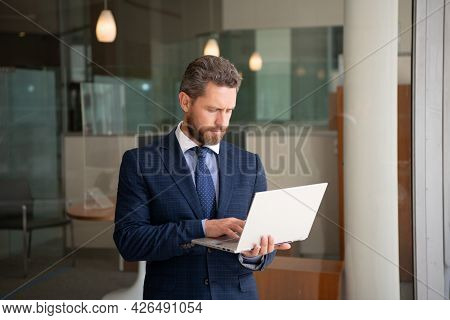 Mature Bearded Ceo Man In Suit Work Online On Wireless Computer Outside The Office, Freelancer.