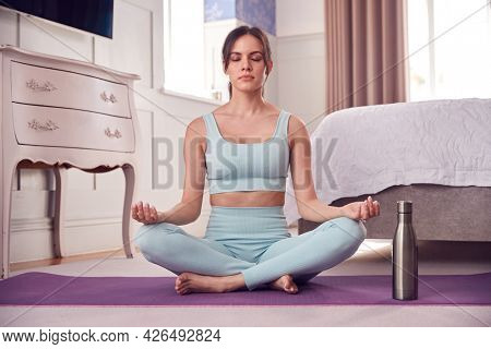 Woman Wearing Fitness Clothing In Bedroom At Home Sitting On Yoga Mat And Meditating