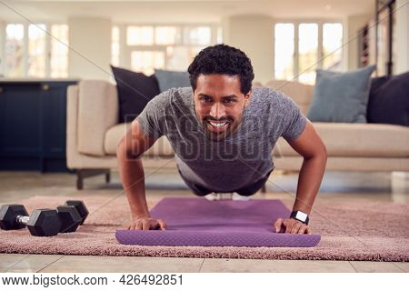 Man In Fitness Clothing At Home In Lounge Doing Press Ups And Exercising With Hand Weights