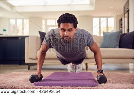 Man In Fitness Clothing At Home In Lounge Exercising With Hand Weights
