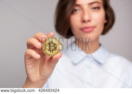 Blurred Woman Demonstrating Golden Bitcoin To Camera After Investing Into Crypto Currency Against Gr