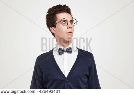 Funny Young Man In Round Glasses Looking Away In Astonishment Against Gray Background
