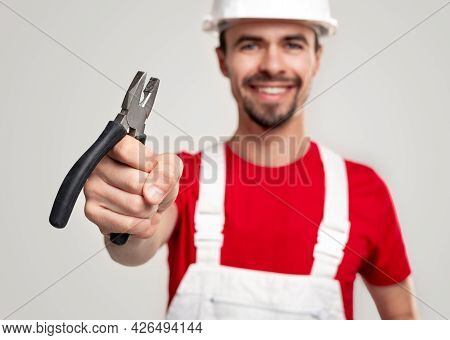 Positive Bearded Male Worker In Overall And Hardhat Demonstrating Pliers While Advertising Professio