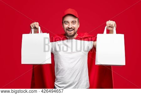 Cheerful Bearded Delivery Man In Red Cap And Superhero Cloak Demonstrating Blank White Paper Bags Wh