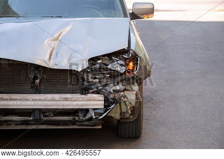 Crumpled Car Stands On Road With Broken Hood After Car Accident With Nobody. Wrecked Car That Cannot