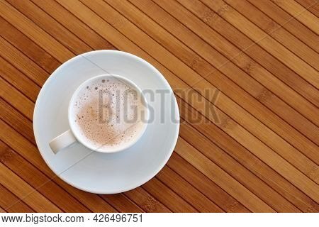Cup Of Cappuccino Coffee In A White Saucer On Wooden Table, Top View