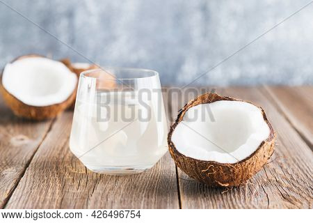 Coconut Water In A Glass Close-up On A Wooden Table And A Half Of A Fresh Coconut Lies Nearby. Organ