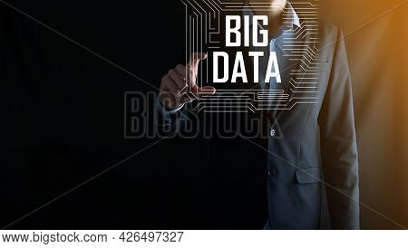 Businessman In A Suit On A Dark Background Holds The Inscription Big Data. Storage Network Online Se