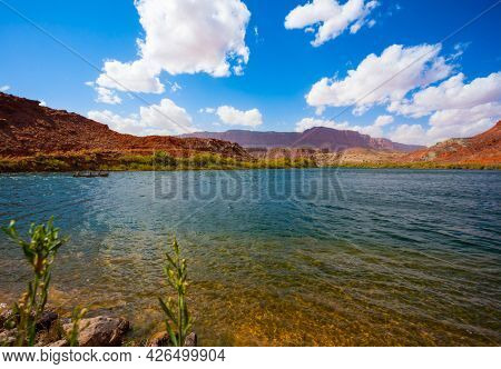 The magnificent Colorado River. Wide river and banks of red sandstone. Lee's Ferry is a historic boat ferry across the Colorado River. USA. The concept of active, extreme and photo tourism
