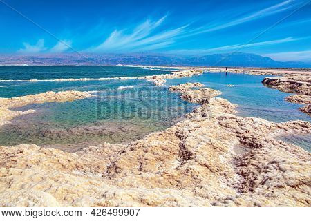 The Israeli coast of the Dead Sea. Windy spring day. The evaporated salt protrudes above the water. Cirrus clouds fly in the blue sky.