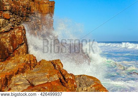 South Africa. White foam of the ocean surf. Powerful ocean surf. Cape of Good Hope at the southern tip of the Cape Peninsula. Bright sunny summer february day