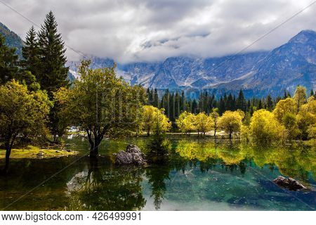 Lake Fuzine in Northern Italy. The Dolomites are covered with clouds. Magnificent colors of autumn. Orange and yellow trees are reflected in the green smooth water.