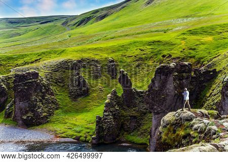 The gray-haired and brave man photographs the canyon Fyadrarglyufur. The most beautiful and mysterious canyon in Iceland. Cloudy summer day. The concept of active, eco and photo tourism