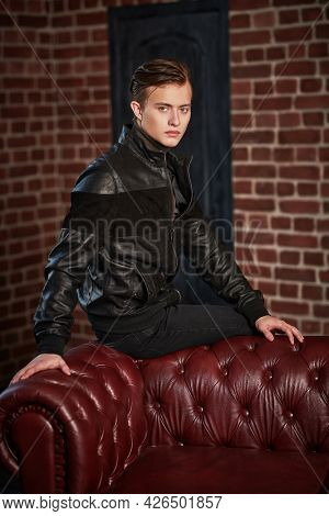 Fashionable young man in black leather jacket sits on a leather sofa in loft apartments. Men's fashion. Lifestyle.