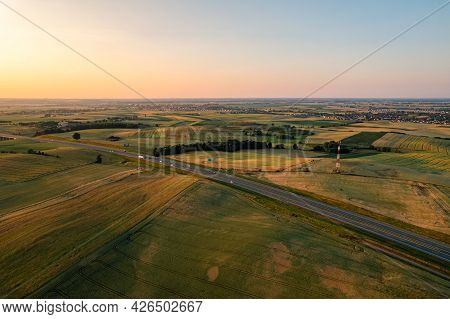 Aerial View Of Highway Or Motorway Beetween Fields In A Countryside During Sunset