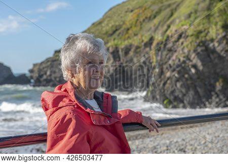 Smiling Senior Women In Eighties, Relaxing With Beach View