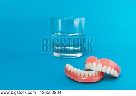 Full Removable Plastic Denture Of The Jaws. A Set Of Dentures On A Blue Background. Two Acrylic Dent