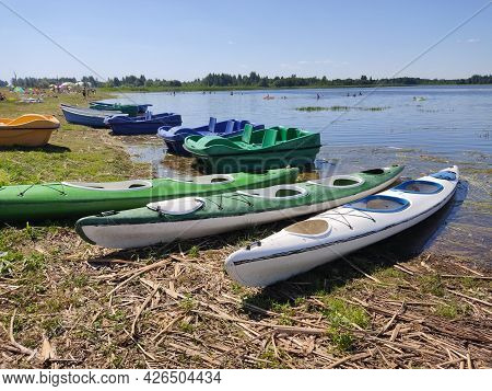 Kayaks And Pleasure Boats On The Shore Of A Calm Lake. Recreation Area With Recreational Watercraft