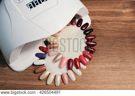 Top View Of Uv Led Gel Nail Drying Lamp And Nail Polish Color Swatch On The Manicure Table.
