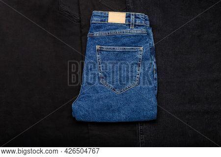 Blue Jeans Denim Pants On Black Denim Jeans Textile Texture Fabric Background. Top View.