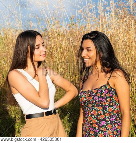 Two Friends Looking At Each Other In A Sunny Day With Tall Grass Behind