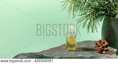 Glass Bottle Of Essential Pine Oil On Grey Stone On Mint Green. Advertising Banner.