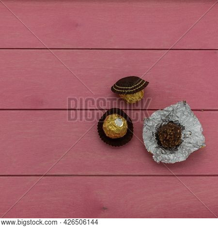 Chocolate Candies Wrapped In A Golden Foil Lie On A Pink Wooden Table. One Candy Deployed. Top View.