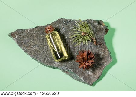 Essential Pine Oil In Glass Bottle With Cone And Twig On Grey Stone Granite On Mint Green. Top View.
