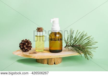 Small Glass Bottles With Essential Pine Oil, Green Twig, Cone On Wooden Saw Cuts On Mint Green.