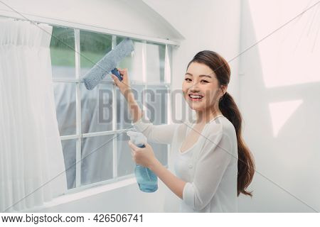Young Smiling Woman Is Cleaning Windows In A House, Doing Chores.