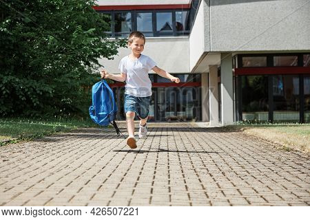 Happy Boy Running From School At The End Of The School Day With A Backpack In Hand. The Beginning Of