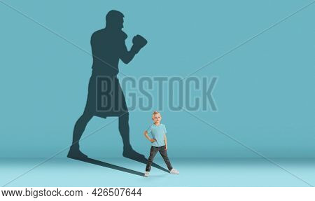 Childhood And Dream About Big And Famous Future. Conceptual Image With Boy And Shadow Of Strong Male