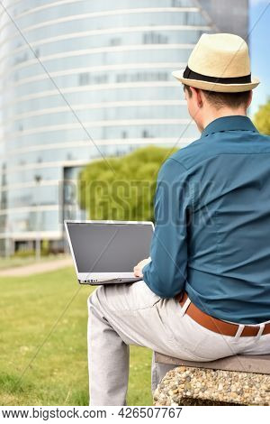 Man Working On A Laptop Computer Outdoors On The Background Of An Office Building In The Downtown. F