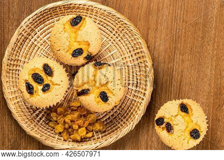 Top View Of Raisin Sponge Cupcake With Pile Of Dried Sweet Raisin In Bamboo Tray And Single Raisin S