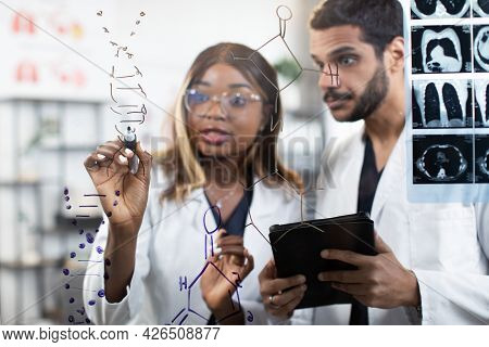 Close Up Portrait Of Two Diverse Scientists Doctors Chemists, Standing Together Near Glass Wall At B