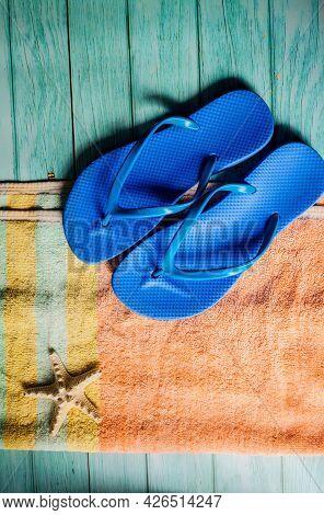 Beach Accessories On Blue Wooden Floor. Top View. Towel And Flip Flops