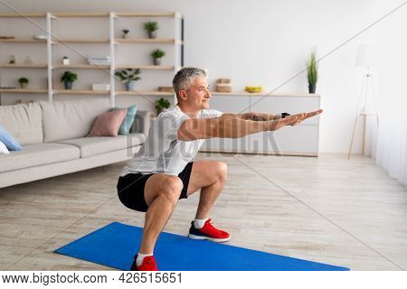 Stay Home Alone To Workout. Fit Mature Man In Sportswear Doing Squats In Living Room Interior, Exerc